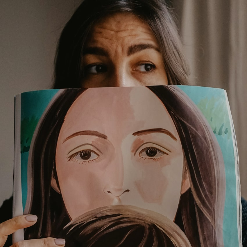 Person holding a painting in front of their face