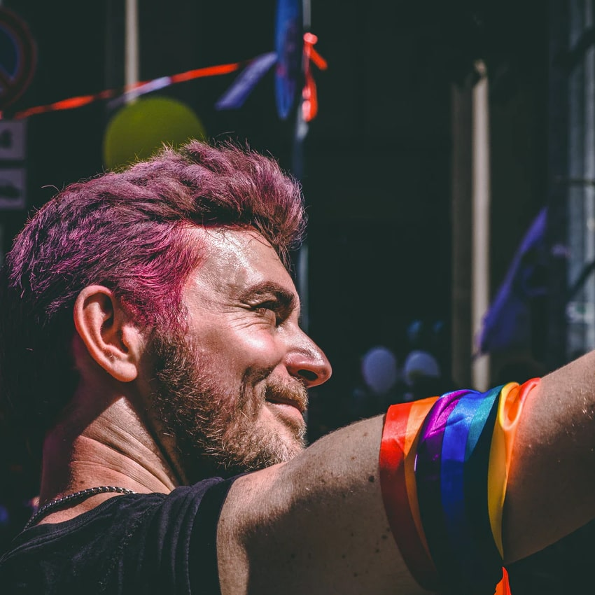 Person with short lilac coloured hair and rainbow ribbon around their arm